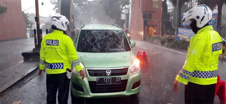 Petugas Polresta Malang Kota tetap melakukan melakukan penyekatan meskipun diguyur hujan deras. (ist)