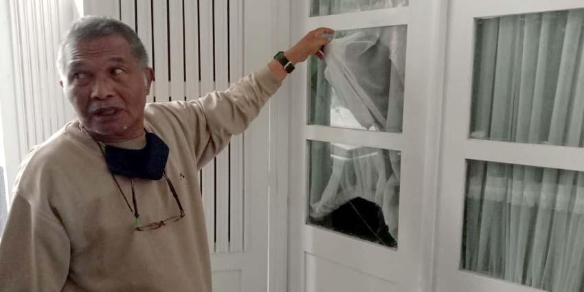 Agus Hadi, salah satu saudara korban menunjukan kaca pintu rumah yang dipecah pelaku. (ist)