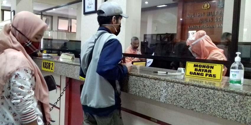 PROTOKOL COVID-19: Petugas pelayanan yang ada di KB Samsat Malang Kota saat melayani wajib pajak kendaraan bermotor. (memo x/fik)