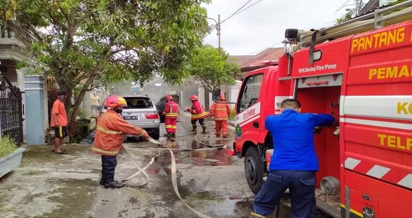 Petugas PMK Kita Malang saat memadamkan mobil BMW yang terbakar. (ist)